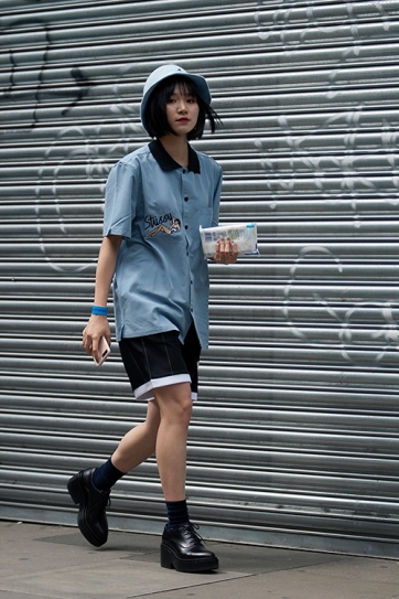 Street Style from day one of Graduate Fashion Week 2017 at the Truman Brewery, London on 4th June 2017. Image shows Graduate Fashion Student Qiqi Zhang, 张启奇 wearing a Stussy shirt, shorts and a Kangol hat.