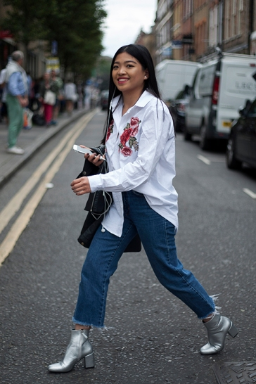 Street Style from day one of Graduate Fashion Week 2017 at the Truman Brewery, London on 4th June 2017. Image shows Womenswear fashion student Cabrini Roy wearing an emboidered shirt from new Look, vintage denim jeans with boots from Zara.