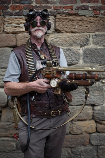 Whitby SteamPunk Weekend July 2017. Image shows a man dressed in SteamPunk style, wearing a headset with goggles and holding a weapon, both made by himself.