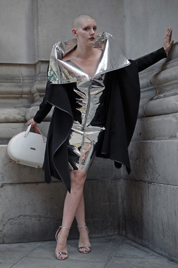 Street Style from Day one of London Fashion Week, Spring Summer 2018, on Friday September 15th 2017. Image shows performer Amy Kingsma wearing a silver and black dress by Gareth Pugh, with a bag and matching silver high heels.