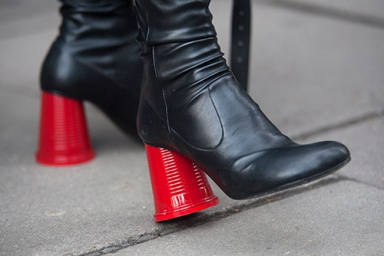 Street Style from day one of London Fashion Week Mens AW 2018. Image shows close up detail of a pair of red and black high heel ankle boots