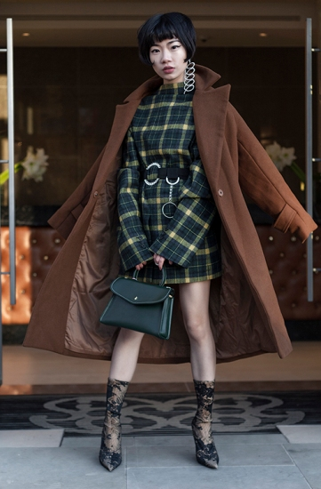 Street Style from day two of London Fashion Week Mens AW 2018. Image shows Chinese fashion buyer Harper Silin. She wears a belted reversed men's jacket as a backless dress, with a statement earring, a handbag and ankle boots.