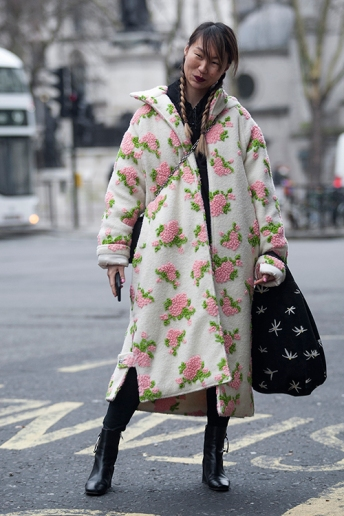 Street Style from day three of London Fashion Week Mens AW 2018. Image shows Kelly Wong from China. She wears a coat by Ryan Lo, a small Louis Vuitton bag and a large Baggu bag.