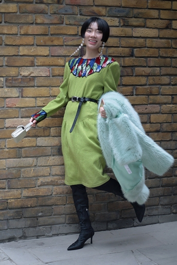 Street Style from day three of London Fashion Week AW 2018. Image shows fashion buyer and influencer Harper Silin, from China, wearing a vintage 1980s knitted dress with sequin detail and boots, styled by Pat Lyttle.