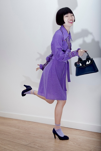 Image shows Chinese Fashion influencer Harper Silin, seen here wearing a vintage purple lurex dress from the 1960s, with socks and heels, and a bag by GB David
