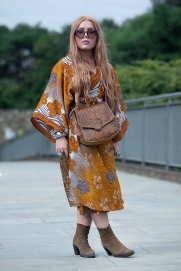 Image shows various people attending the Classic Car Boot Sale, held at granary Square, Kings Cross in London, on Saturday August 18th. Many people that attended dressed up in vintage fashion clothing and style. This is Devon from South East London. She wears a vintage silk kimono style dress with cowboy boots, sunglasses from Primark, and a snake skin bag.
