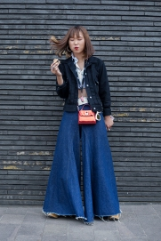 Image shows various people attending the Classic Car Boot Sale, held at granary Square, Kings Cross in London, on Saturday August 18th. Many people that attended dressed up in vintage fashion clothing and style. This is Anna from Tochigi, Japan. She wears a black denim jacket by Japanese fashion brand GU, a vintage blouse, cool statement denim super wide flared trousers by Maison Margiela, and a red bag and sunglasses.