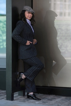 Street Style on the second full day of London Fashion Week SS 2019, Saturday 15th 2018. Image shows LA based Video Producer Cindy Martin dressed in a pinstripe men's cut suit, with a 1970s mens shirt, a tweed cap and customised patent Oxford heel brogues.