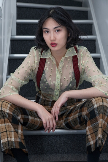 Fashion styling by Pat Lyttle. Image shows Film graduate Xaio Giao Wang from China, dressed in a vintage 1970s yellow sheer top, with her own black lace bra, check print trousers and braces.