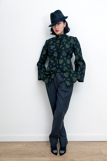 Fashion styling by Pat Lyttle. Image shows Film graduate Xaio Giao Wang from China, dressed in a vintage hat, a 1960s Mandarin collar dress coat and mens trousers, with high heels by Pied A Terre..