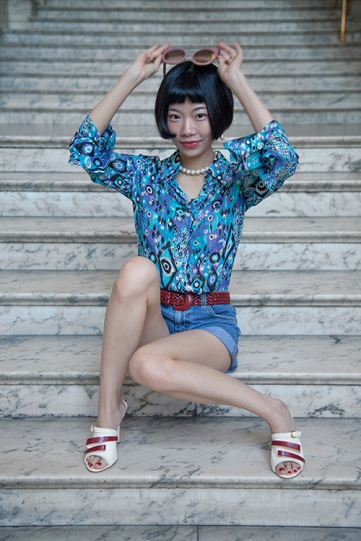 Image shows Chinese fashion buyer, PR, blogger and Influencer Harper Silin. Harper wears a vintage ensemble of belted 1970s denim shorts with a silk print blouse, sunglasses by ASociety and the most stunning shoes by designer Michael Azu, all styled by Pat Lyttle.