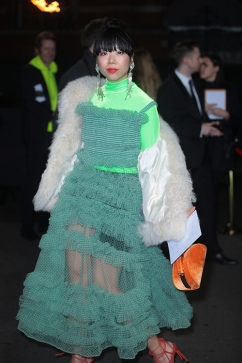 Guests arrive at The Fashion Awards 2018 by the BFC and sponsored Swarovski, and held at the Royal Albert Hall in London on December 10th 2018. Image shows Fashion journalist and elite style blogger, Susanna Lau / Susie Bubble. She wears earrings by Alessdra Rich, a top by Halpern Studio, a bag by Topshop, a dress by Molly Goddard, and red high heel sandals.