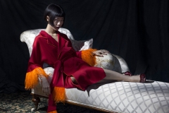 Image shows fashion loving Chinese Influencer and blogger, Harper Silin, at a photo-shoot styled and photographed by Pat Lyttle, with assistance of Rod Leon. Harper wears a Chinese themed red robe by OSMAN with feather detail, and high heeled mules