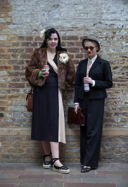 Wayne Hemingway's Classic Car Boot Sale at London's Kings Cross Peninsular, where vintage fashion and style, mix with entertainment and classic cars, for fans of preloved style. Image shows attendees Lifeofbell and Leah both dressed in Vintage style.