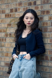 Street style on day 3 of London Fashion Week Mens on June 9th 2019. Image shows a portrait of Tracy from China, in a vintage top and bag, with jeans by Urban Outfitters