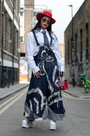 Street style on day 3 of London Fashion Week Mens SS 2020. Image shows a very dapper woman called Dee, who wears shoes by Club Exx Clothing, dungarees by c8y8s Caitlin Yates, and a hat by Sacred Halk Clothing