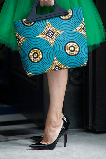 Street style shot on day two of Africa Fashion Week London 2019. Image shows a woman's legs in black patent high heels, with a Dutch printed cotten bag with a bold turquoise hand bag.