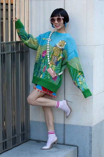 Street Style on day two of London Fashion Week SS 2020 on Friday September 13th 2019, showcasing stylish individuals London is internationally known for. Image shows stylish LFW favourite Chinese fashion fan, Harper Silin. She wears a decorative knitwear top with shorts by Uooyaa, a mini bag with pearl chain by Gofefe, clear high heel shoes by Public Desire, with socks by Topshop and sunglasses by A Society.