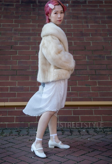 Street style in London on Sunday 8th March 2020. Fans of vintage style showcase their individuality. Image shows Missy from China. She wears a vintage fur coat. a top and dress from a Chinese designer called Furlu & Lilly and shoes by Chanel.