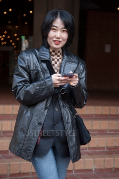 Street style in London on Sunday 8th March 2020. Fans of vintage style showcase their individuality. Image shows Zhen from China. She wears a vintage leather jacket, a top bought in China, and jeans from the high street