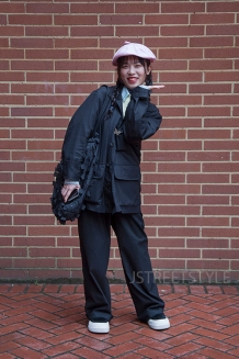 Street style in London on Sunday 8th March 2020. Fans of vintage style showcase their individuality. Image shows Shun Shing Shau from China. She wears a hat from a vintage shop, a jacket and top by Uniglo, a bag by COS.
